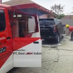 Salah seorang pekerja DoorJek sedang mencuci mobil salah seorang pelanggan yang dipesan melalui aplikasi cuci mobil online.