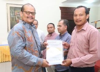 Ketua Bapomi Sumut Dr H Muhammad Isa Indrawan SE MM menyerahkan SK Korda Bapomi dan Artipena kepada utusan perguruan tinggi.
