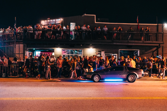 Themed bars and wild cars are lined up throughout the crossroads during First Fridays