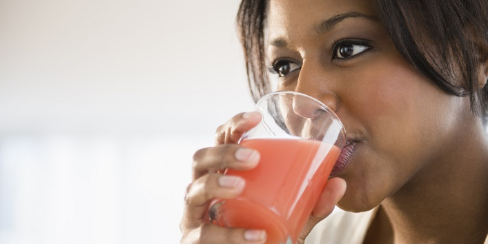 African American woman drinking glass of juice