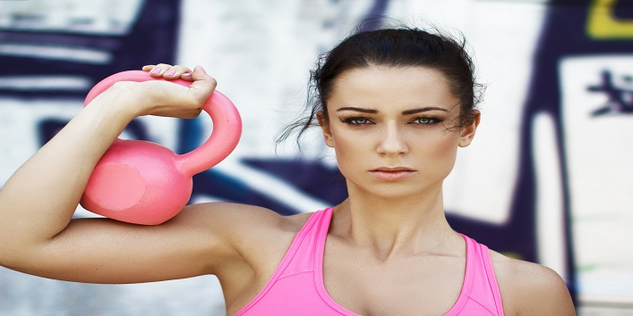 Woman holding pink kettlebell over shoulder, outdoor sport