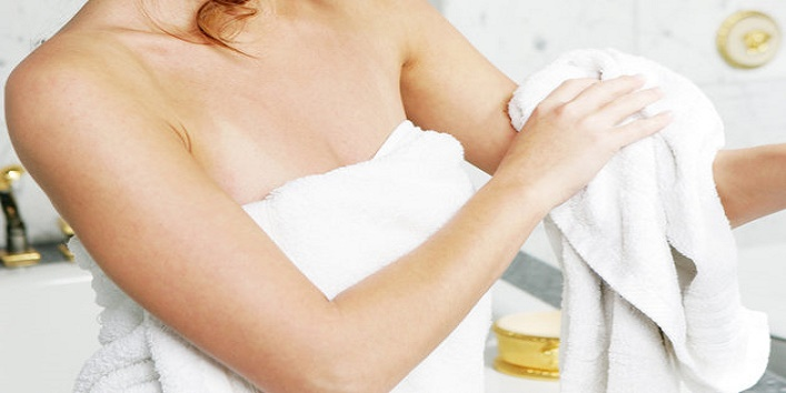 Young woman in bathroom, rubbing herself dry with towel