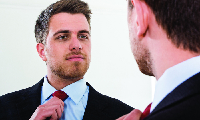 Vain businessman looking in the mirror to show narcissistic job seekers are being rewarded