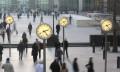 Business men and women walk past clocks, hr