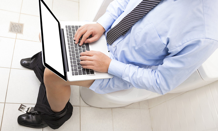 Man sitting working on the toilet at home before work