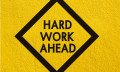 yellow sign warning of hard work ahead