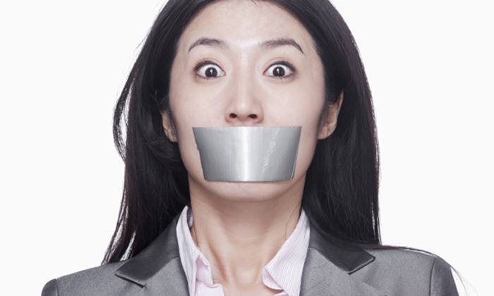 Woman taped mouth to show women and minorities being penalised for promoting diversity
