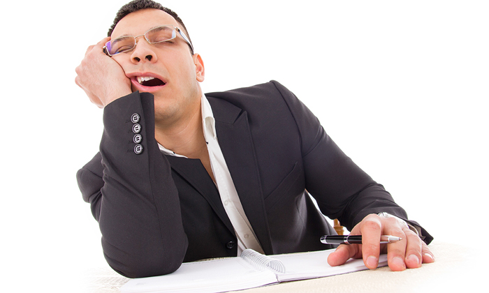 Sleepy worker yawning to show how to manage sleepy employees