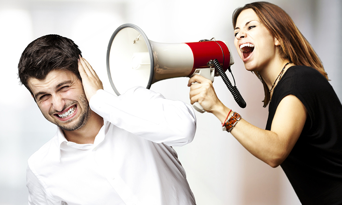 Woman yelling at man through megaphone
