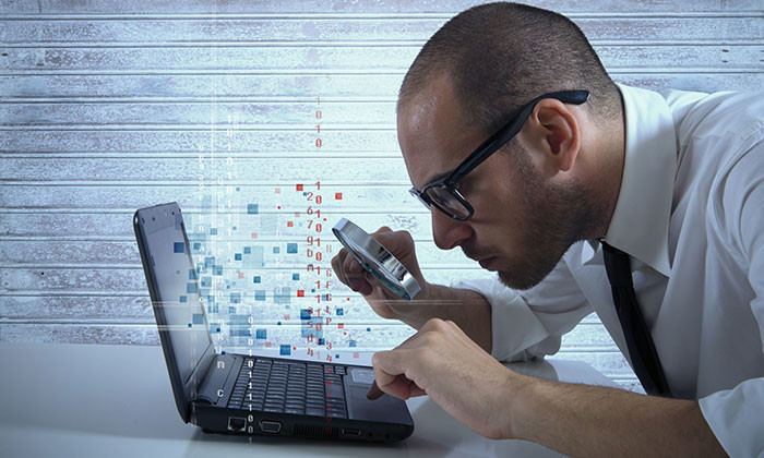 business man holidng magnifying glass over computer - 123RF