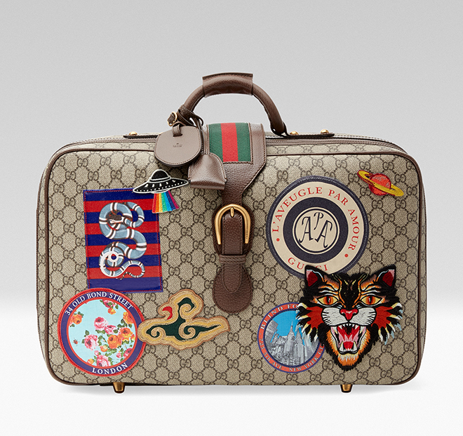 With the new rules of classic elegance, it might be time to re-look your travel accessories, starting with brave steps across the airport terminal toting the new Gucci Courrier GG Supreme suitcase. Travel continues to be a source of inspiration for Alessandro Michele. A collection of bags in the GG motif is enriched with a blend of contemporary embroideries-like the UFO-and vintage inspired details, including airmail trims. The appliqués are individually embroidered and then skillfully hand-applied to each piece by specialized artisans. This process ensures that no two items will be alike, giving each a one-of-a-kind appearance.