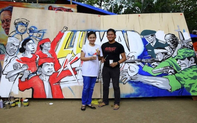 Gerilya artists Janno Gonzales and Mar Rios with their work in progress. The mural aims to bring awareness to the Lumad crisis in Mindanao. Photo by  Bernard Testa, InterAksyon.com.