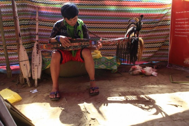 A member of the Lumad group plays the 'kudyapi,' a two-stringed musical instrument created by particular tribal groups in Mindanao. Photo by Bernard Testa, InterAksyon.com.