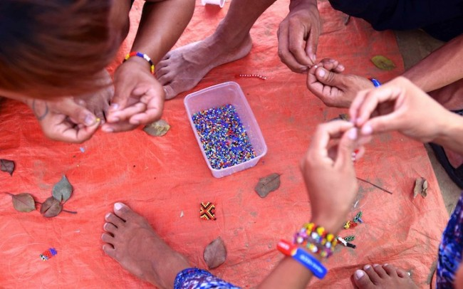 The creative hands of these Lumads who have set camp in Manila are stringing beads to make their colorful jewelry. Photo by Bernard Testa, InterAksyon.com.