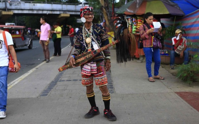 A Lumad elder dressed in traditional attire takes a break after performing some traditional songs with his 'kudyapi.' Photo by Bernard Testa, InterAksyon.com.