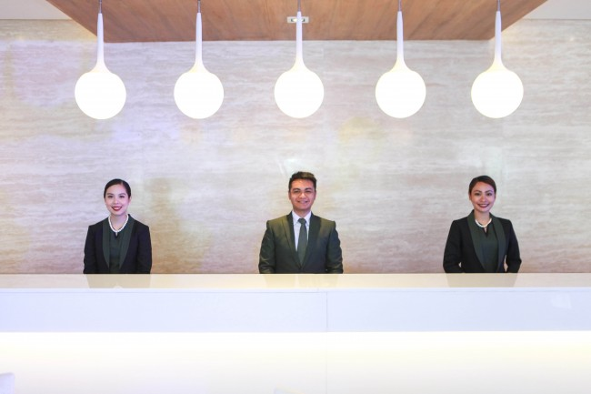 At the front desk reception area of Hotel 101, staff members warmly welcome guests as they aim to offer excellent customer service. Photo courtesy of Hotel 101.