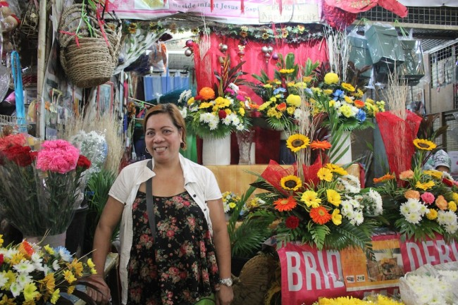 Lovie Pascual has her sleeping quarters at the back of her flower stall, which is open 24/7. Photo by Chad De Guzman, InterAksyon