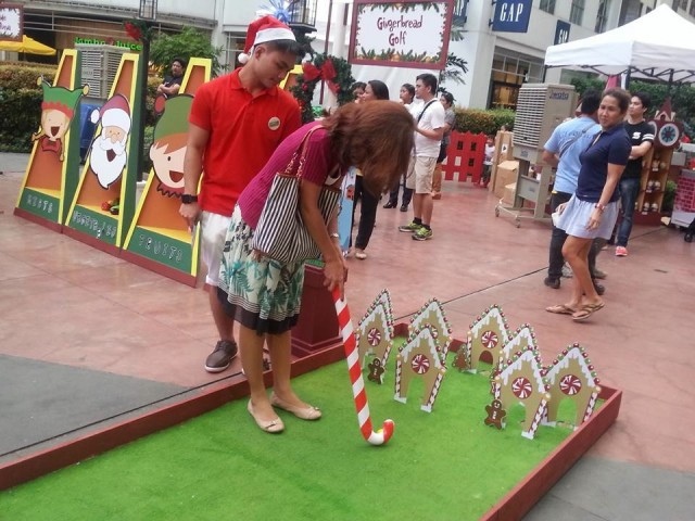 A mall goer tries her putting skills at the Gingerbread Golf booth of Robinsons Supermarket's Give Wellness fair, November 5, 2016. Photo by Francine M. Marquez, InterAksyon.