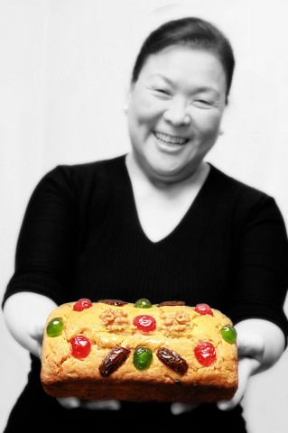 Baker and 'Fruitcake Queen' Ju.D holds her famous creation. Photo courtesy of Ju.D Lao.