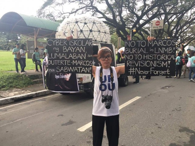 A student shows placards with a political message during UP Diliman's annual Lantern Parade, December 16, 2016. InterAksyon photo.