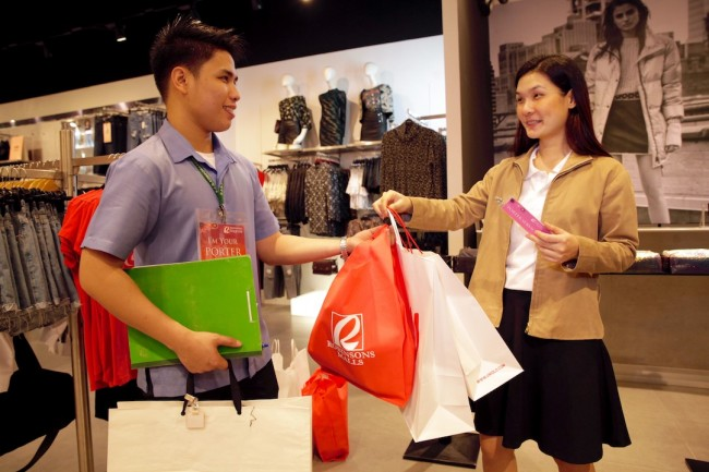 At Robinsons Magnolia, a trained porter (left) helps a shopper carry her shopping bags while the latter goes about her holiday shopping. The award-winning malls' free porter service runs till January 30, 2016. Photo by Bernard Testa, InterAksyon.
