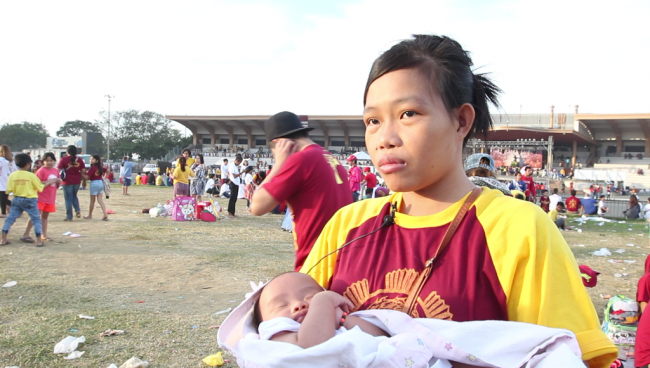 Mary Jane Paojana, shown here with her two-month old  baby, attend the Traslacion festivities, January 9, 2017. Photo by Neil Portugal, InterAksyon.