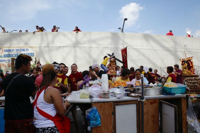 Devotees participating in the 'traslacion' procession take their lunch break in a congee vendor's makeshift stall. Photo by Bernard Testa, InterAksyon.