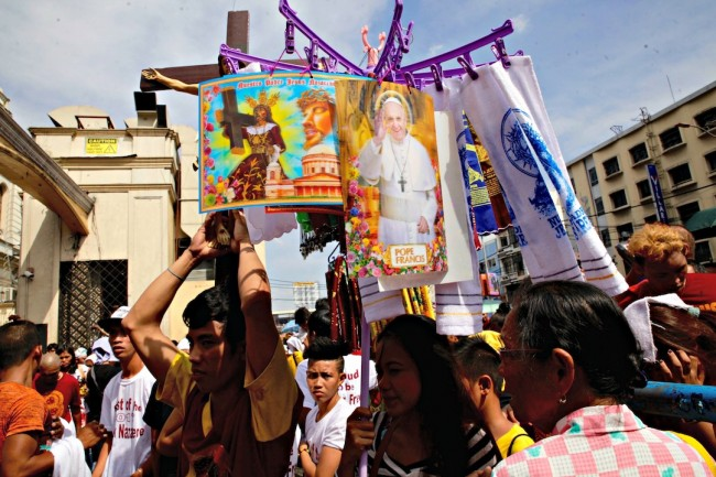 A vendor sells posters of the Black Nazarene and Pope Francis during the 'traslacion' procession on January 9, 2017. Photo by Bernard Testa, interaksyon.