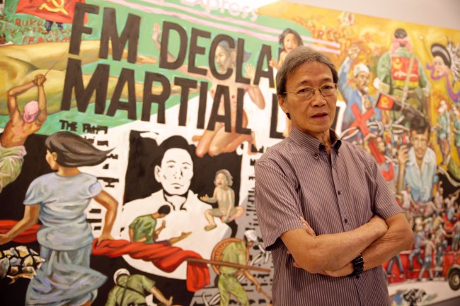 Social realist artist Pablo Baens Santos with his mural 'Martial Law in the Philippines,' which is one of the works at the exhibit with the AR feature. Photo by Bernard Testa, InterAksyon.