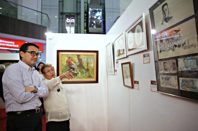Artist Romi Mananquil shows RLB president Frederick Go his flora and fauna series of banknotes and coins that he was commissioned to do for Bangko Sentral ng Pilipinas in the 80s. Photo by Bernard Testa, InterAksyon.