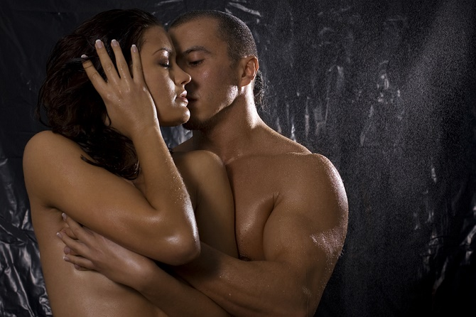 Loving affectionate nude heterosexual couple in shower engaging in sexual games, hugging and kissing
