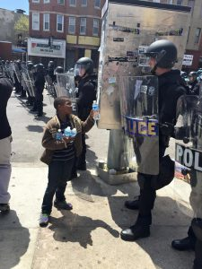 14-Young Boy Offers Bottles Of Water To Policemen During A Hot Day In Baltimore