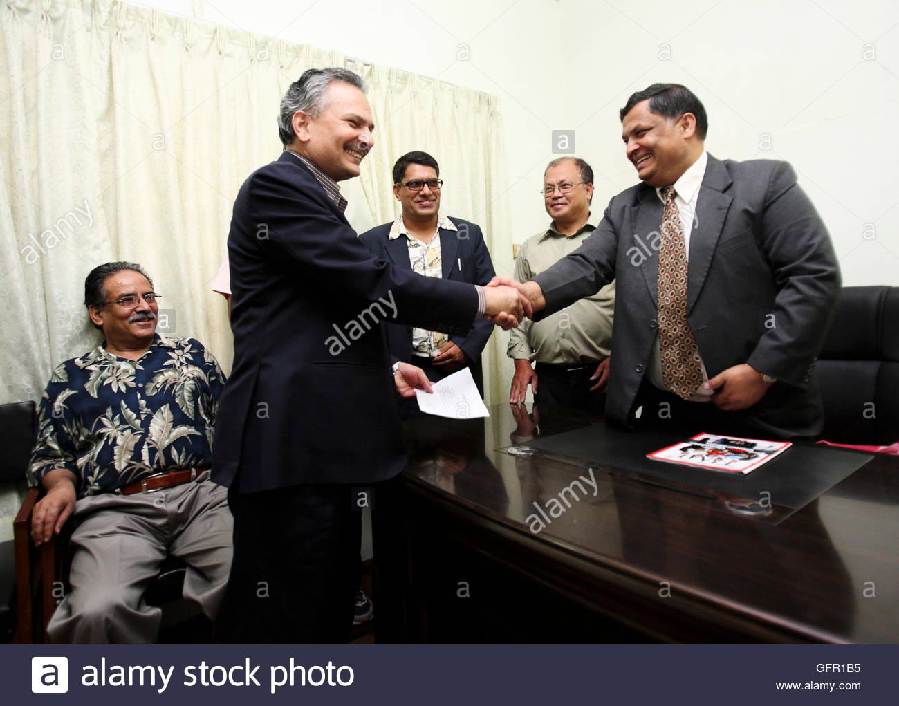 Maoist senior leader Dr. Baburam Bhattarai (L) shakes hand after receiving his nomination paper from Manohar Prasad Bhattarai, Special Secretary of the Nepali Parliament while filing his nomination for the Prime Minister's post in Kathmandu August 26, 2011. Candidates from Communist Party of Nepal (Maoist) and Nepali Congress has filed their nominations for Nepal Prime Minister's post on Friday for the election to be held on Sunday. REUTERS/Navesh Chitrakar (NEPAL - Tags: POLITICS ELECTIONS)