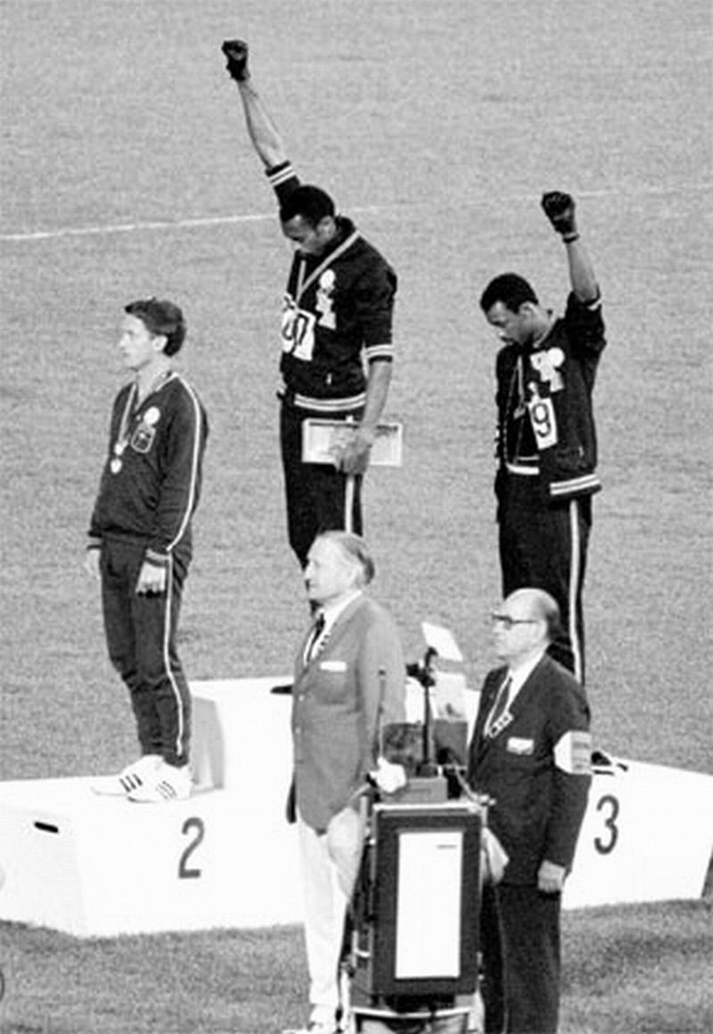 1968 کے میکسکو اولمپک میں 200 میٹر دوڑمقابلہ جیتنے کے بعد گولڈ میڈل پانے والے ٹامی اسمتھ (بیچ میں) اور کانسہ تمغہ پانے والے جان کارلوس (دائیں) نے کالے داستانے پہن کر اپنے ہاتھ اٹھاکرسیاہ-فام کے خلاف ہونے والے امتیازات کی مخالفت کی تھی۔ چاندی تمغہ کے فاتح پیٹر نارمن (بائیں) نے بھی دونوں کھلاڑیوں کے ساتھ یکجہتی دکھائی تھی۔ (فوٹو بشکریہ : peconicpublicbroadcasting.org)