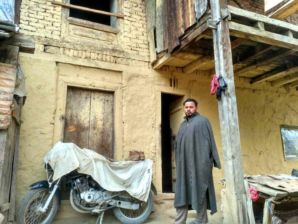 اپنے گھر کے باہر فاروق احمد ڈار (فوٹو : مجید مقبول(