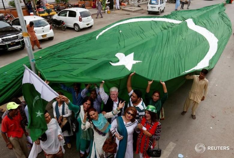 Supporters of civil rights group for transgender people, the Gender Interactive Alliance (GIA), dance and chant slogans as they pose with a national flag ahead of the Independence Day in Karachi, Pakistan