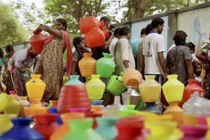 پانی بھرنے کے لئے کھڑے مقامی لوگ (فائل فوٹو : پی ٹی آئی)