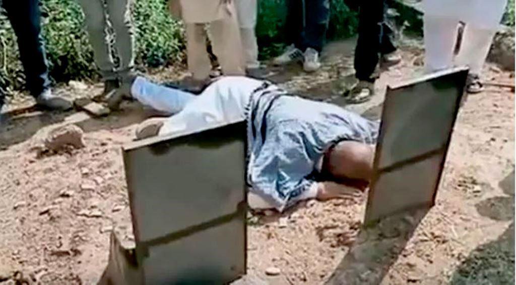 دہشت کے الزام سے بری ہونے کے 23 سال بعد سرینگر میں اپنے والد کی قبر پر محمد علی بھٹ (فوٹو بہ شکریہ : ویڈیو گریب)