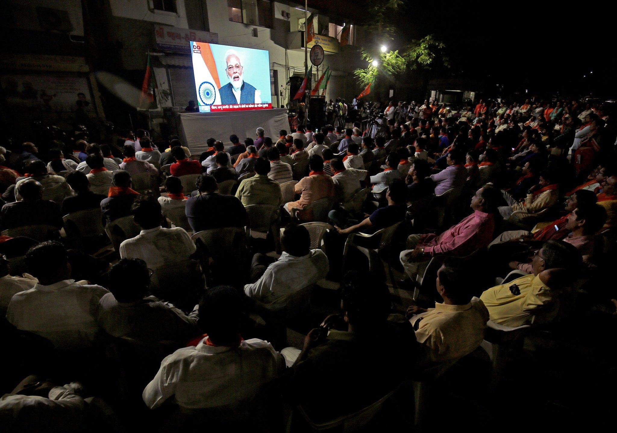8 اگست کو احمد آباد میں وزیر اعظم نریندر مودی کا ملک کے نام خطاب سنتے لوگ(فوٹو : رائٹرس)