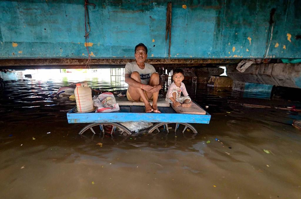 بہار کی راجدھانی پٹنہ کے ایک سیلاب متاثر ہ علاقے میں ٹھیلہ پر بچے کےساتھ بیٹھا شخص۔ (فوٹو : پی ٹی آئی)