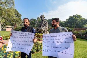 پارلیامنٹ میں مظاہرہ کرتے پی ڈی پی کے راجیہ سبھا ممبر میر فیاض اور نذیر احمد لوائے (فوٹو : پی ٹی آئی)