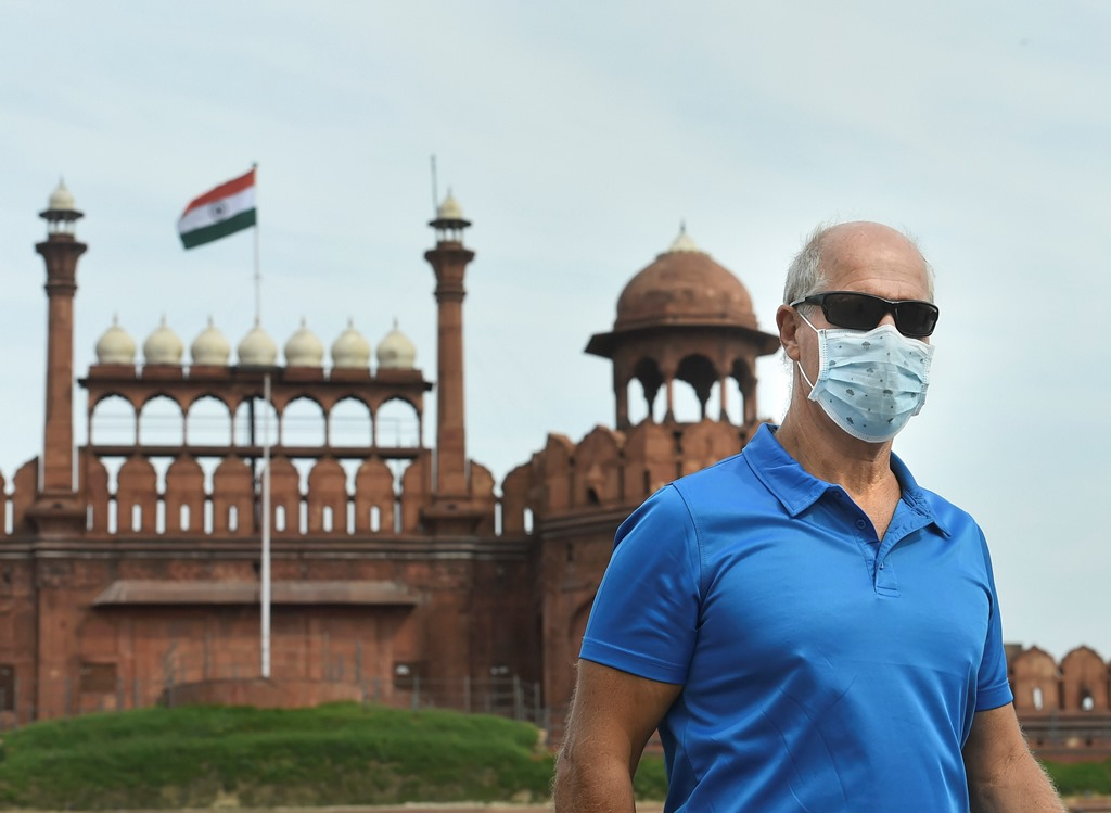 دہلی واقع لال قلعہ کے پاس ماسک لگائے ایک سیاح۔ (فوٹو : پی ٹی آئی)