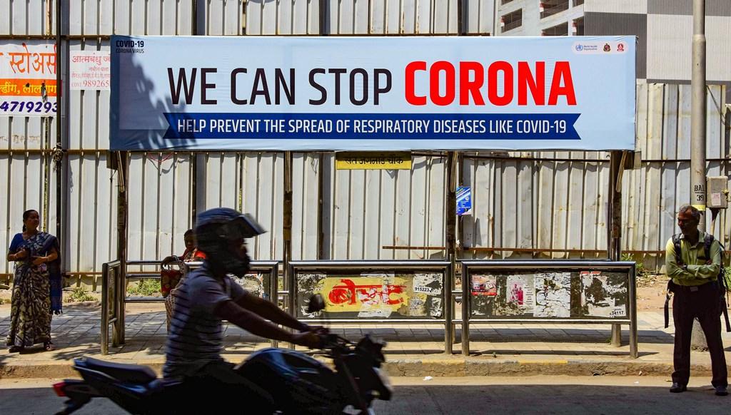 ممبئی کے ایک بس اسٹینڈ پر کورونا وائرس کو لےکر بیداری پھیلانے کےلئے لگا ایک بل بورڈ۔ (فوٹو : پی ٹی آئی)