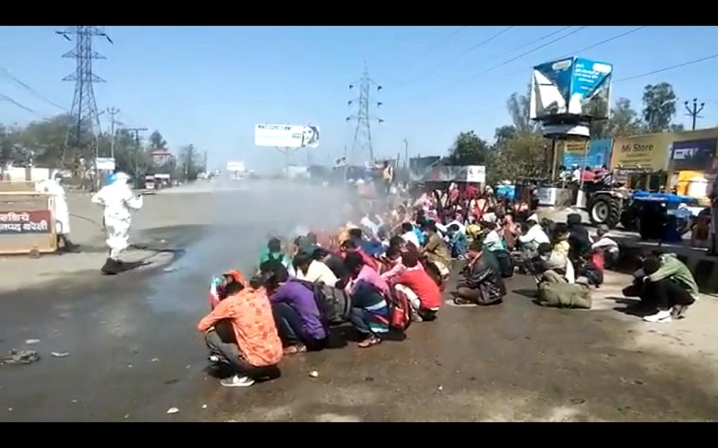 اتر پردیش کے بریلی میں گھر واپس لوٹے مزدوروں کو سینٹا ئزر سے نہلایا جا رہا ہے۔ (فوٹو: ٹوئٹر/ویڈیو گریب)