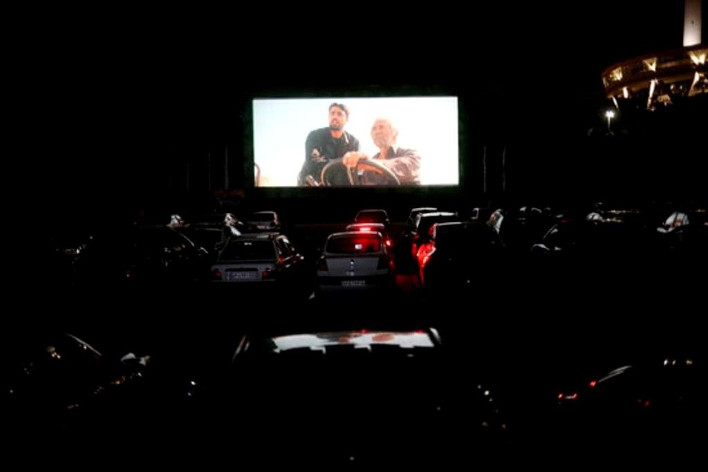 ایران کی راجدھانی تہران کے میلاد پارکنگ ایریا میں ڈرائیو ان تھیٹر کا مزہ لیتے لوگ(فوٹو: رائٹرس)