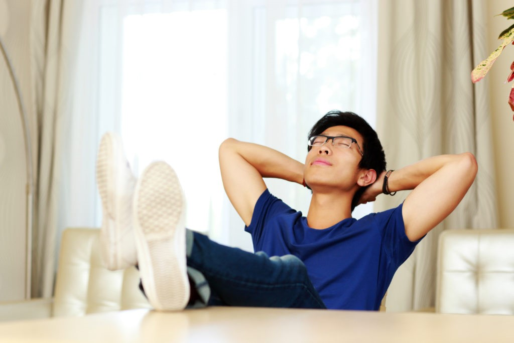 Asian man relaxing at home. He doesn't have to worry about the trouble to find tutors.