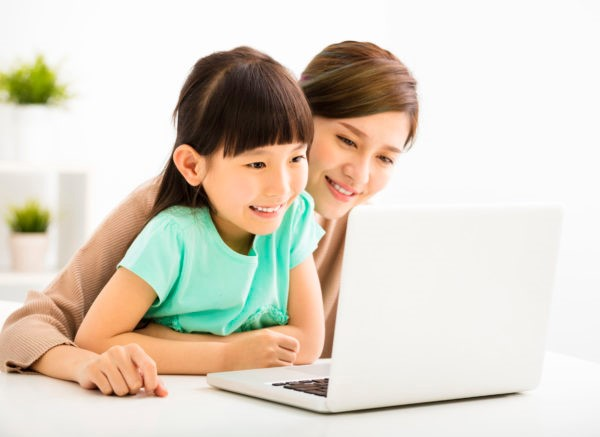 Girl looking into laptop with mother