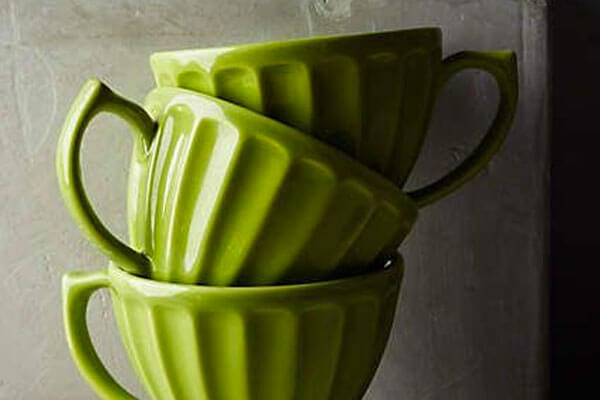 green coloured tea cups and coasters