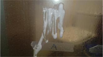 將梳打粉糊搽上浴屏上,感覺有點像牙膏。