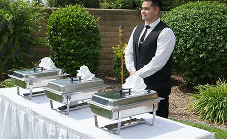 A Waiter Standing near a Buffet Counter  - Event Catering Services Upland by Panzarello Catering